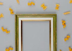 vista superior de macaronis como farfalle fusilli penne ao redor da moldura em fundo azul com espaço de cópia
