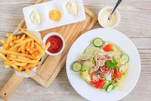 Batatas fritas e ketchup em um prato de madeira e salada com legumes frescos e atum, vista superior com espaço livre para o seu texto.