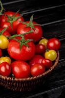 vista lateral de tomates amarelos e vermelhos em uma cesta com fundo de madeira