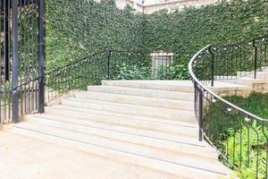 paisagem no jardim do parque. escada de pedra com corrimão de ferro e grama verde, flores e árvores ao redor