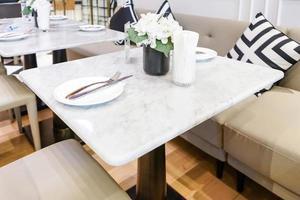 mesa de jantar e cadeiras confortáveis em estilo vintage com elegante configuração de mesa