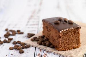 bolo de chocolate com grãos de café em uma mesa de madeira