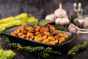 macarrão frito com amêijoas em um prato preto foto