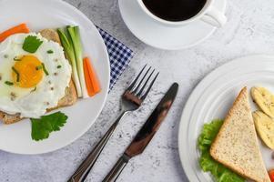 um ovo frito na torrada coberto com sementes de pimenta com cenoura e cebolinha foto