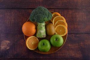 fatias de laranja com maçã, kiwi e brócolis em uma placa de madeira