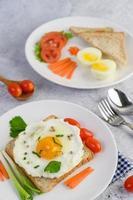 um ovo frito com torradas, cenouras, milho bebê e cebolinhas foto