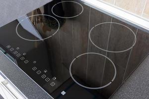 close-up de uma placa de vitrocerâmica de cozinha elétrica com móveis de cozinha