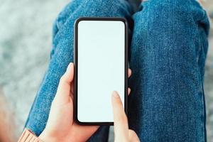 mão segurando maquete de tela em branco do smartphone em cima da mesa foto