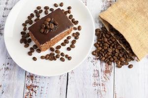 Bolo de chocolate com grãos de café em uma superfície de madeira foto