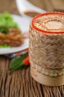 caixa de bambu para arroz pegajoso em uma mesa de madeira foto