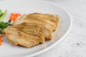 peito de frango cozido no vapor em um prato branco com cebolinhas e cenouras foto