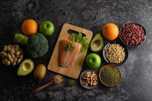 legumes, frutas e peixes salmão em uma tábua de madeira foto