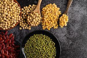 legumes e feijão sortidos em uma superfície de cimento preto foto