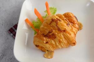 croissant com aperitivo de cachorro-quente em prato branco foto