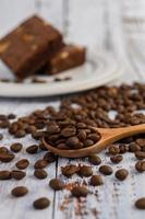 grãos de café na colher de pau e brownies de chocolate em uma mesa de madeira branca