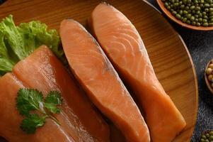 pedaços de salmão em um prato de madeira foto