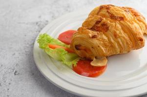 um croissant com cachorro-quente no prato branco