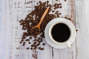 grãos de café e uma xícara de café na mesa branca