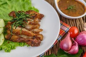Pescoço de porco grelhado em um prato branco com cebola roxa, tomate e pimenta em uma mesa de madeira foto