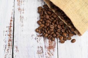 grãos de café em sacos de cânhamo em uma mesa de madeira branca foto