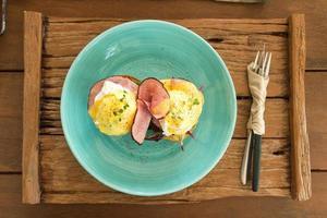 ovos benedict no prato azul foto