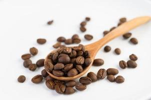 grãos de café em uma colher de pau sobre uma mesa de madeira branca