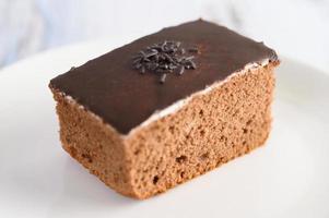 bolo de chocolate em um prato branco e mesa de madeira branca