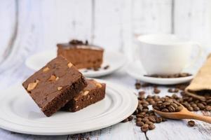 brownies de chocolate em um prato branco e grãos de café em uma colher de pau foto
