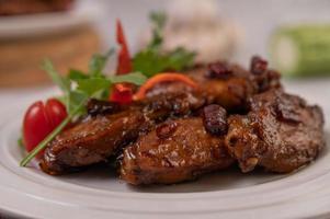 pasta de chili asas de frango frito em uma travessa branca com chili e coentro
