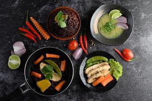 Pratos variados de vegetais, carnes e peixes em um fundo de pedra preta foto