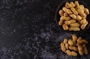 amendoim em um copo no chão de cimento preto foto