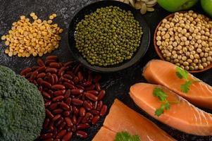 legumes, brócolis, frutas e salmão em um fundo de cimento preto foto
