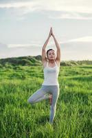 jovem e bela mulher praticando ioga no campo