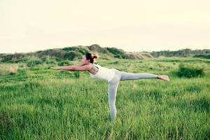 jovem e bela mulher praticando ioga no campo foto