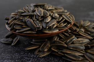 sementes de girassol em uma tigela de madeira na superfície preta foto