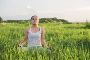 mulher de ioga na postura de lótus em um prado ensolarado