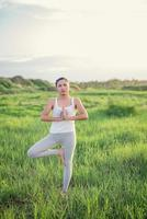 linda mulher de ioga em um prado ensolarado foto