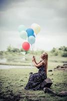 jovem segurando balões coloridos na natureza