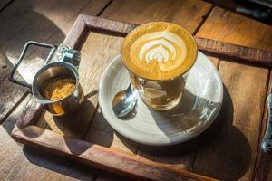 café com latte art na bandeja de madeira ao sol foto