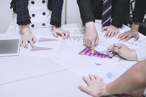 grupo de empresários reunidos em torno de um gráfico