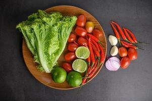 fatias de limão, chalotas, alho, tomate, alface e pimentão em um prato de madeira