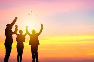 três pessoas celebrando no pôr do sol