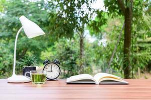 livro com relógio, chá e abajur em uma mesa do lado de fora