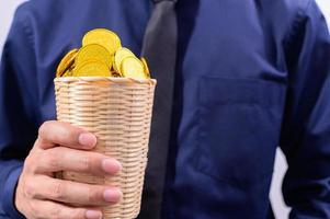 mão segurando uma cesta cheia de dinheiro