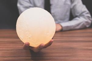 pessoa segurando uma lâmpada lunar em uma mesa foto