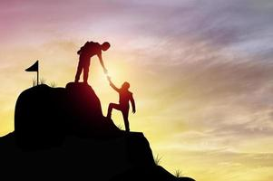 duas pessoas se ajudando a escalar uma montanha