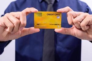 profissional segurando um cartão de crédito amarelo