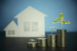 pilha de moedas com uma casa nos fundos foto