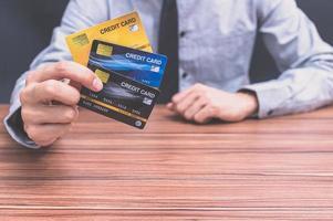 pessoa segurando três cartões de crédito