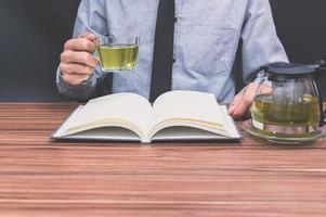 pessoa bebendo chá enquanto lê um livro